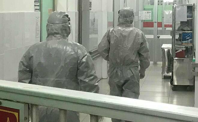 Thứ trưởng Y tế Nguyễn Trường Sơn cùng bác sĩ Bệnh viện Chợ Rẫy mặc đồ bảo hộ vào phòng cách ly thăm 2 bệnh nhân đang điều trị tại Bệnh viện Chợ Rẫy tối 23/1. Ảnh: Đ.H.