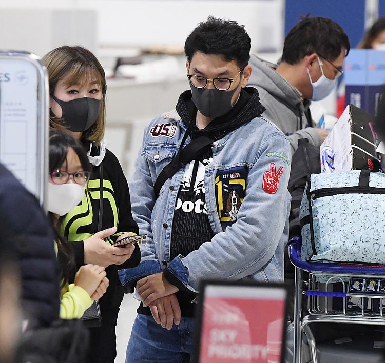 Du khách mang khẩu trang tại sân bay Narita, Nhật Bản sáng 26/1. Ảnh: Reuters.