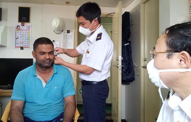 Nhà chức trách đo thân nhiệt người nước ngoài nhập cảnh vào làm việc ở cảng Vũng Áng, thị xã Kỳ Anh. Ảnh: CDC