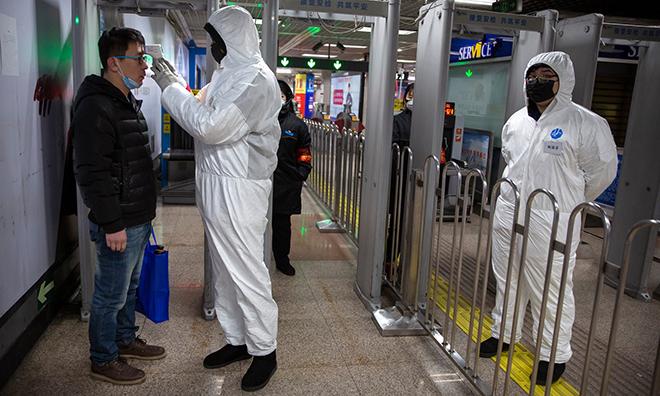 Nhân viên y tế kiểm tra nhiệt độ hành khách tại ga tàu điện ngầm Bắc Kinh. Ảnh: Nytimes