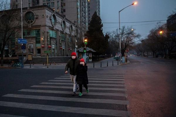 Người dân ở Bắc Kinh đeo khẩu trang và phun thuốc sát trùng để ngăn chặn sự lây lan của sự bùng phát virus. Ảnh: AFP