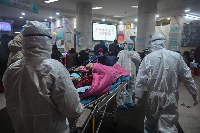 Bác sĩ tại bệnh viện ở Vũ Hán đưa bệnh nhân vào điều trị. Ảnh: AFP