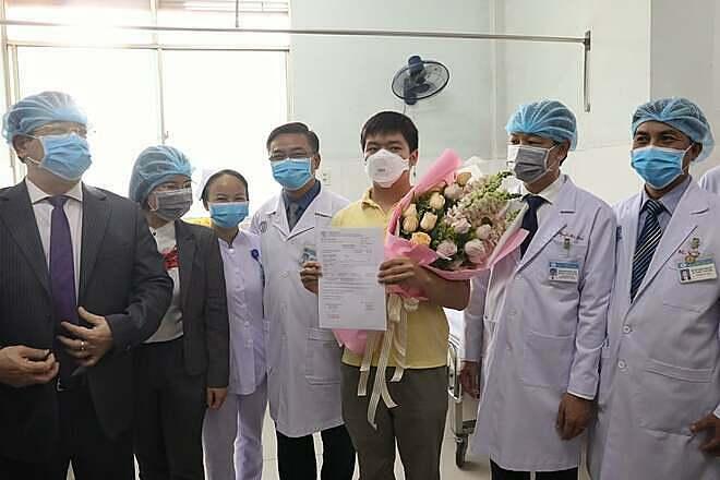 Bệnh nhân chụp ảnh kỷ niệm với y bác sĩ Bệnh viện Chợ Rẫy trước khi xuất viện. Ảnh: Hữu Khoa.