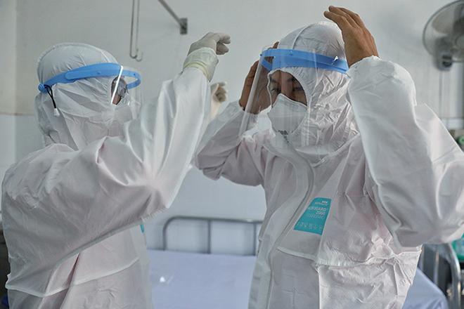 Các bác sĩ Bệnh viện Chợ Rẫy mặc trang phục bảo hộ trước khi vào phòng cách ly bệnh nhân viêm phổi. Ảnh: Hữu Khoa.