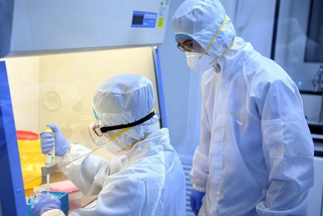 Các nhà khoa học tiến hành xét nghiệm mẫu bệnh phẩm của các bệnh nhân nghi nhiễm virus corona. Ảnh: Xinhua