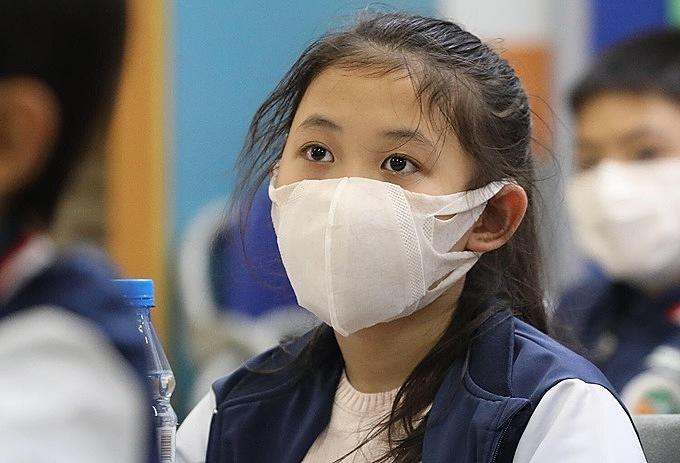 Trẻ đeo khẩu trang mỗi khi ra ngoài giúp phòng tránh lây nhiễm virus corona. Ảnh: Ngọc Thành