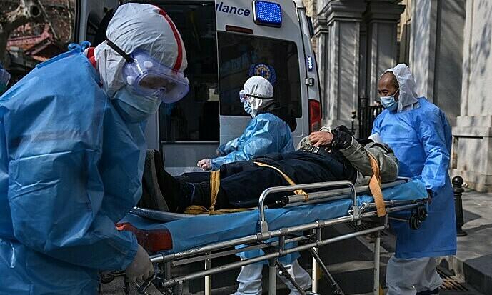 Nhân viên y tế đưa bệnh nhân nghi mắc viêm phổi cấp khỏi một chung cư tại Vũ Hán, Trung Quốc ngày 30/1. Ảnh: AFP.