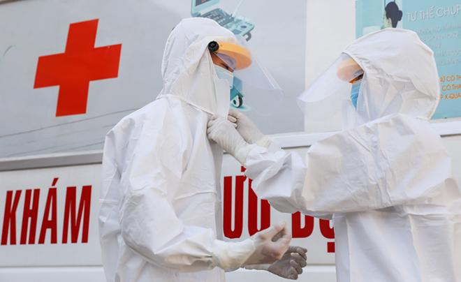 Đội ngũ y bác sĩ trên xe cứu thương, xe vận chuyển người nghi nhiễm virus corona trong trang phục bảo hộ. Ảnh: Như Quỳnh.