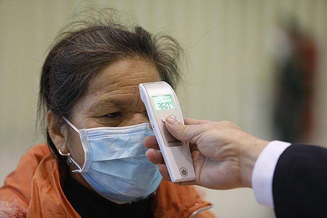 Một người nhập cảnh từ Trung Quốc được kiểm tra thân nhiệt ở cửa khẩu. Ảnh: Giang Huy.