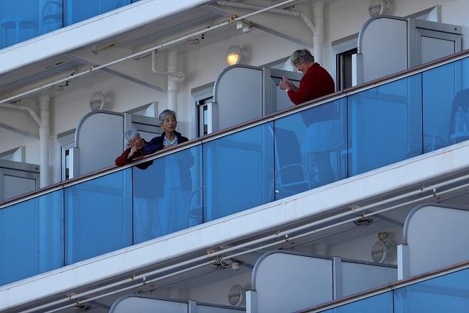 Hành khách trò chuyện và động viên nhau qua ban công. Ảnh: Reuters