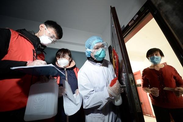 Nhân viên y tế gõ cửa nhà một phụ nữ khi đang tiến hành kiểm tra khu cư dân ở Thiên Tân. Ảnh: Reuters
