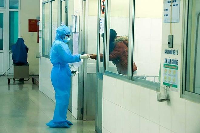 Bác sĩ đưa cơm cho bệnh nhân ở khu vực cách ly. Ảnh: Nguyễn Đông.