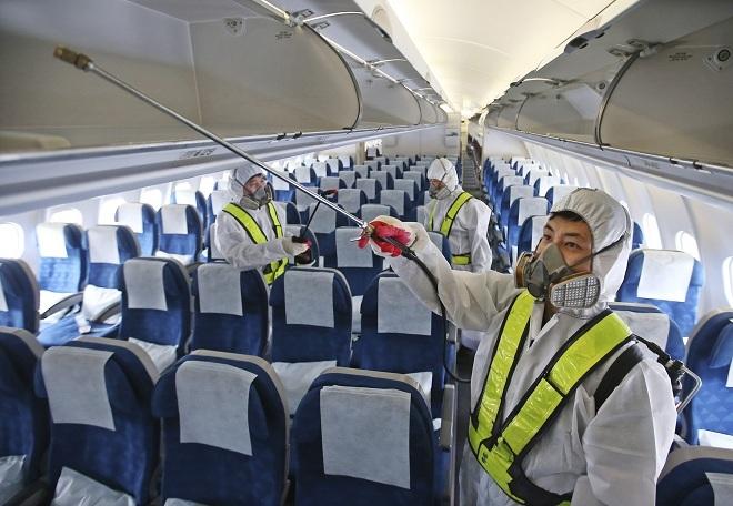 Nhân viên hãng hàng không đang khử trùng máy bay. Ảnh: AP