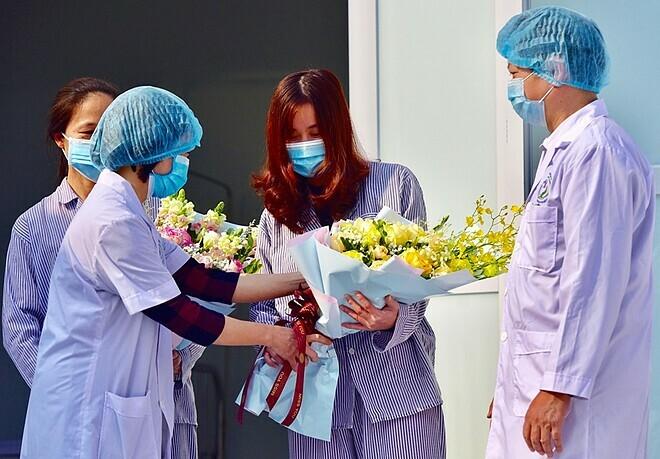 Bệnh nhân Nguyễn Thị Nam nhậnhoa từ bác sĩ khi xuất viện, người mặc áo sọc bên trái là bệnh nhân Phạm Thị Bình. Ảnh: Giang Huy.