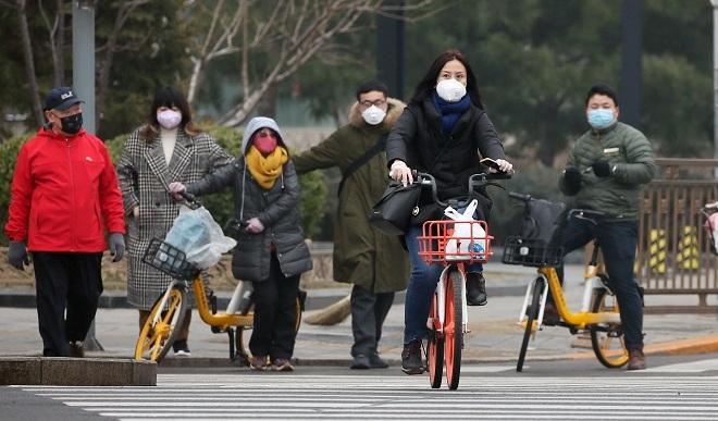 Người dân Bắc Kinh đeo khẩu trang đi làm vào ngày 18/2. Ảnh: Reuters