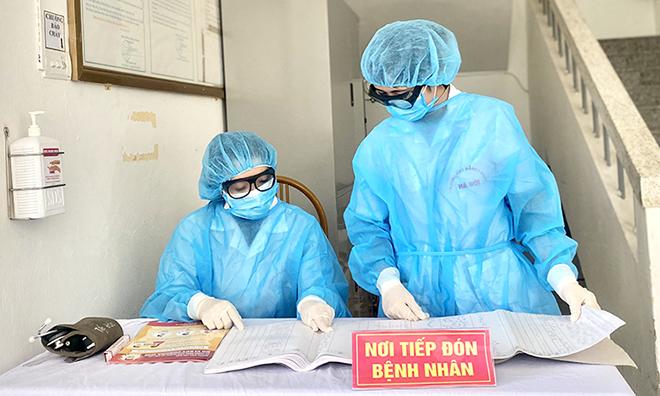 Nhân viên y tế, bệnh viện Đa khoa Hà Đôngtúc trực tại quầy tiếp đón. Ảnh: Thùy An
