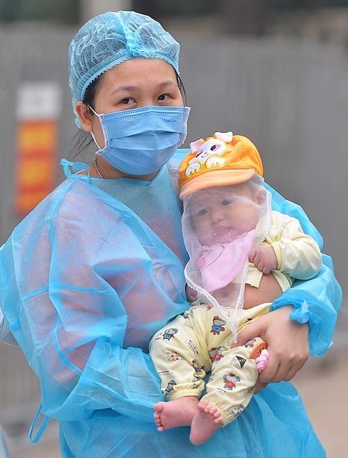 Bé gái khỏe mạnhtrong vòng tay mẹ khi xuất viện. Ảnh: Giang Huy.