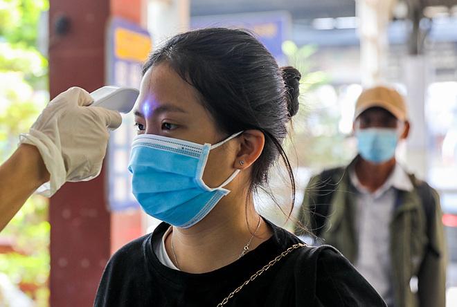 Nhân viên y tế đo thân nhiệt cho hành khách tại Sài Gòn. Ảnh: Như Quỳnh.