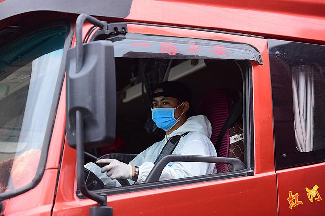 Tài xế mặc đồ bảo hộ khi thông quan hàng hóa tại cửa khẩu đường bộ số II Kim Thành, Lào Cai. Ảnh: Giang Huy.