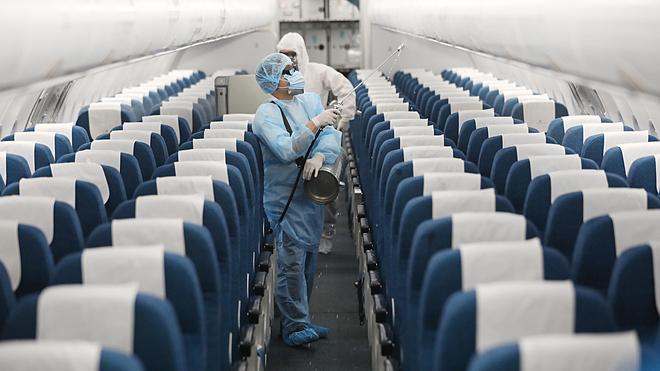 Nhân viên y tế khử trùng máy bay của hãng Vietnam Airline để phòng virus corona. Ảnh: Ngọc Thành.