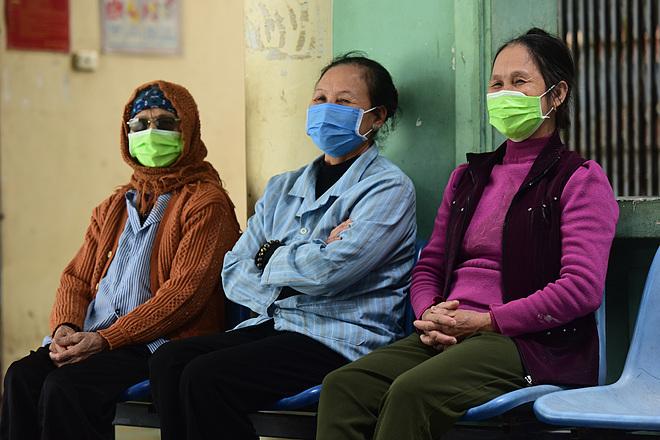 Phía hàng lang đối diện phòng ông Vinh, mẹ ông (ngoài cùng bên trái), cùng hai chị gái ngồi hành lang hóng gió. Họ trong diệncách ly do tiếp xúc gần với bệnh nhân dương tính nCoV. Ảnh: Giang Huy