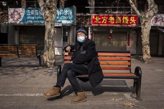 Một cụ ông ngồi trên đường phố Vũ Hán ngày 5/2. Ảnh: Bloomberg