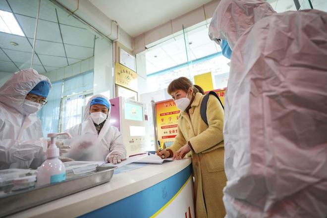 Nhân viên y tế trao đổi với một bệnh nhân tại Vũ Hán. Ảnh: AFP