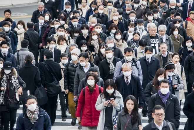 Người dân Trung Quốc đeo khẩu trang nơi công cộng để tránh lây bệnh Covid-19. Ảnh: Bloomberg