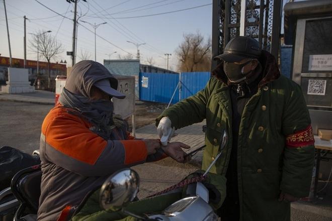 Nhân viên trạm kiểm soát đo nhiệt độ của người dân khi đi vào một ngôi làngở quận Tống Châu, Bắc Kinh ngày 28/2. Ảnh:EPA/Shutterstock