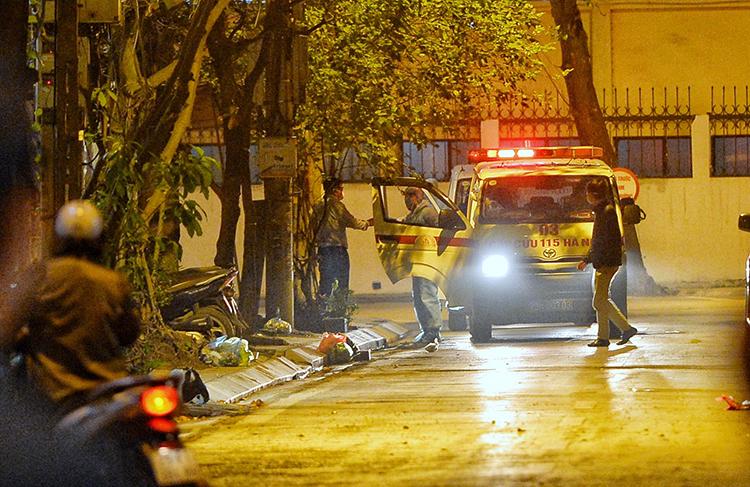 Các nhân viên y tế đến kiểm tra niêm phong số nhà 125 Trúc Bạch, đêm 6/3. Ảnh: Giang Huy.