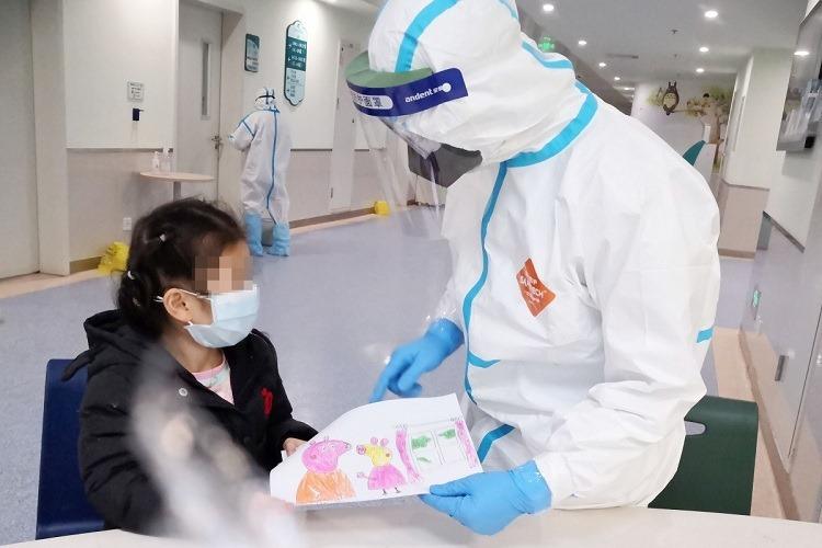 Y tá Yang Liu nhận bức tranh vẽ tay của một bệnh nhân mắc Covid-19 tại Bệnh viện Nhi đồng Vũ Hán vào ngày 28/2. Ảnh: Tân Hoa Xã