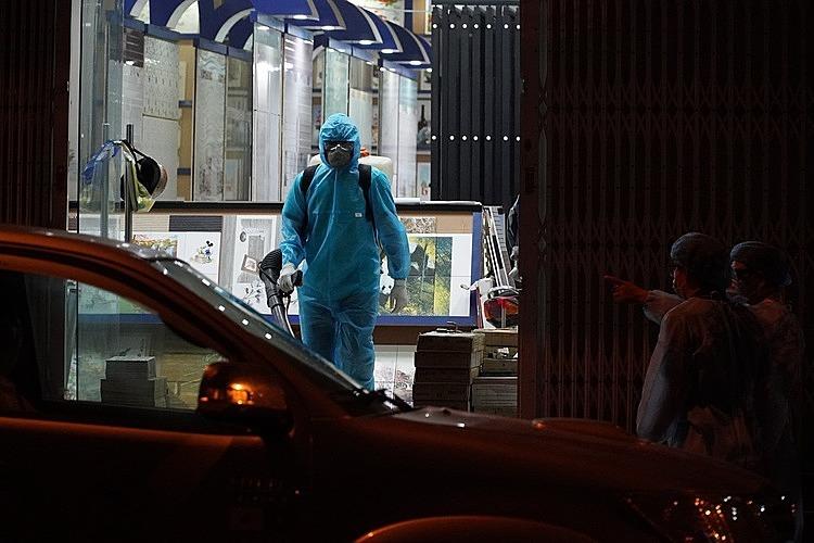 Nhân viên y tế phun thuốc khử khuẩn cửa hàng của bệnh nhân 34 tại thành phố Phan Thiết, Bình Thuận, tối 10/3. Ảnh: Việt Quốc.