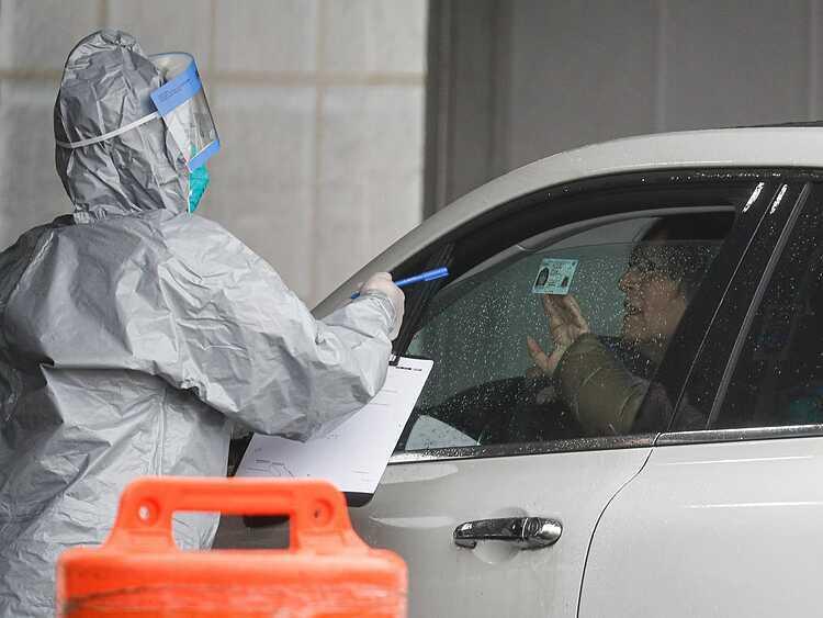 Người dân tại Mỹ xuất trình thẻ căn cước để xét nghiệm tại một trạm lưu động ngày 13/3. Ảnh: AP