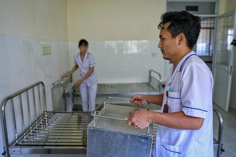 Nhân viên y tế chuẩn bị giường cho Bệnh viện Điều trị Covid-19,ngày 15/3. Ảnh: Hữu Khoa.