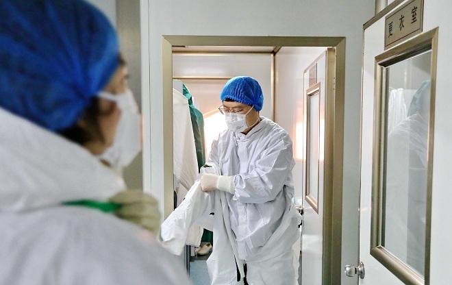Nhân viên y tế Trung Quốc mặc đồ bảo hộ trước khi vào phòng cách ly. Ảnh: Reuters