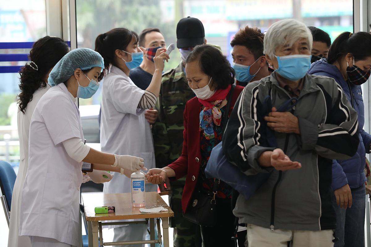 Bệnh nhân đến khám tại Bệnh viện K được các y bác sĩ đo thân nhiệt, rửa tay, đeo khẩu trang phòng dịch, ngày 17/3. Ảnh: Ngọc Thành.