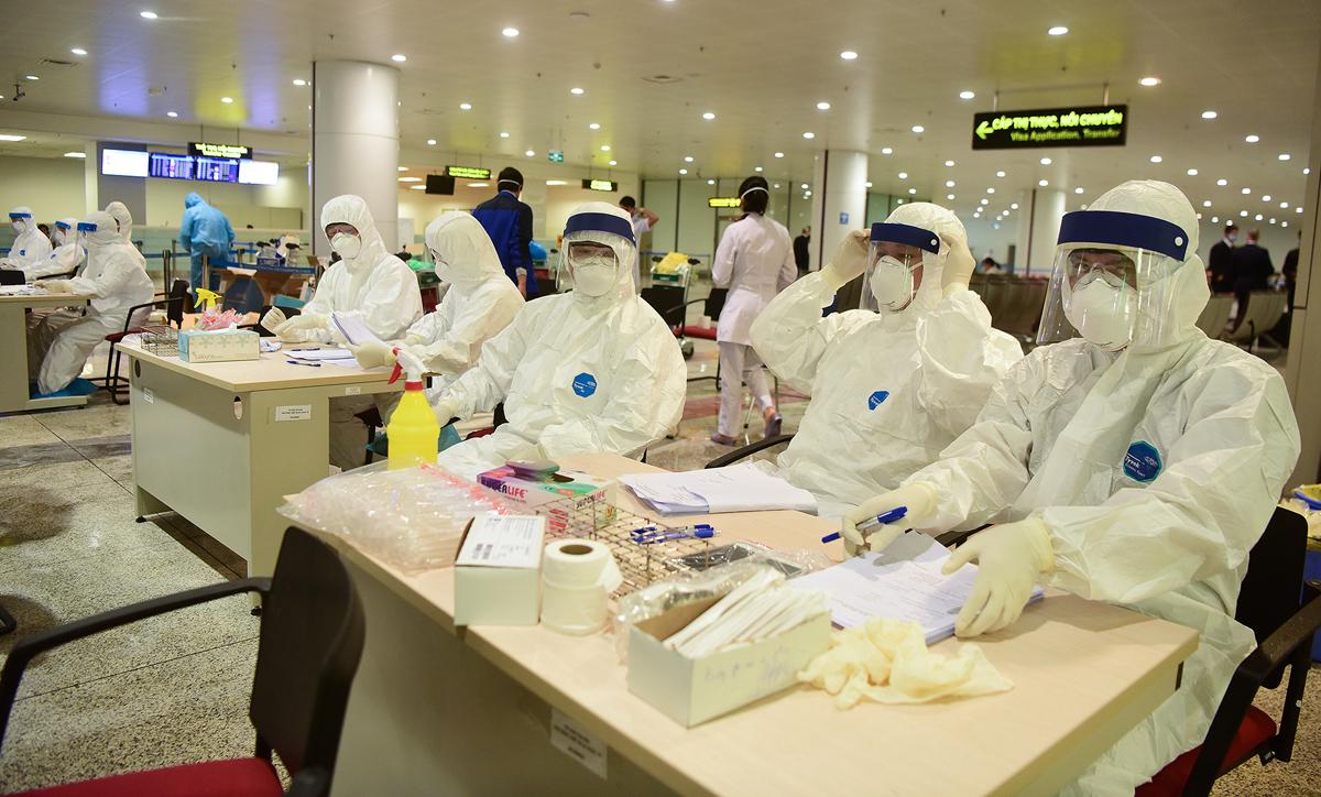 Các nhân viên y tế trực lấy mẫu bệnh phẩm khách nhập cảnh sân bay Nội Bài để xét nghiệm nCoV. Ảnh: Giang Huy.