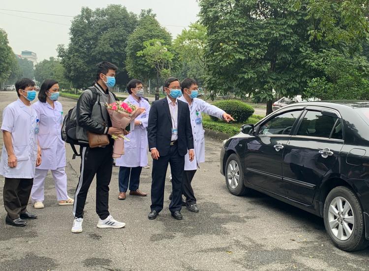 Bệnh nhân 18 (ôm hoa)sáng 20/3 được xe của bệnh viện Ninh Bình đưa về nhà ở huyện Vũ Thư, tỉnh Thái Bình, và cách ly giám sát y tế tại nhà. Ảnh: Mỹ Hạnh.