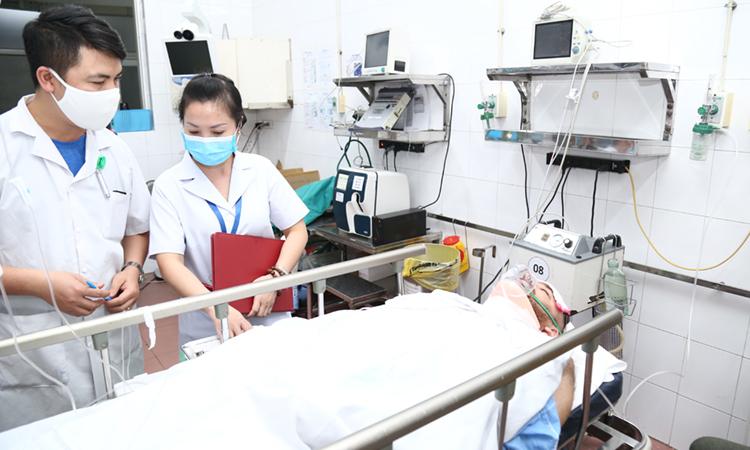 Y bác sĩ Bệnh viện Hữu nghị Việt Đức thăm khám bệnh nhân Iraq bị chấn thương đốt sống cổ. Ảnh: Thảo My.