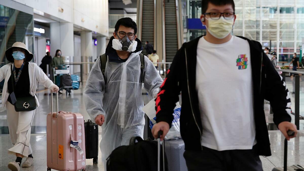 Người dân Hong Kong mặc đồ bảo hộ và đeo mặt nạ phòng độc để tránh lây nhiễm Covid-19. Ảnh: Reuters