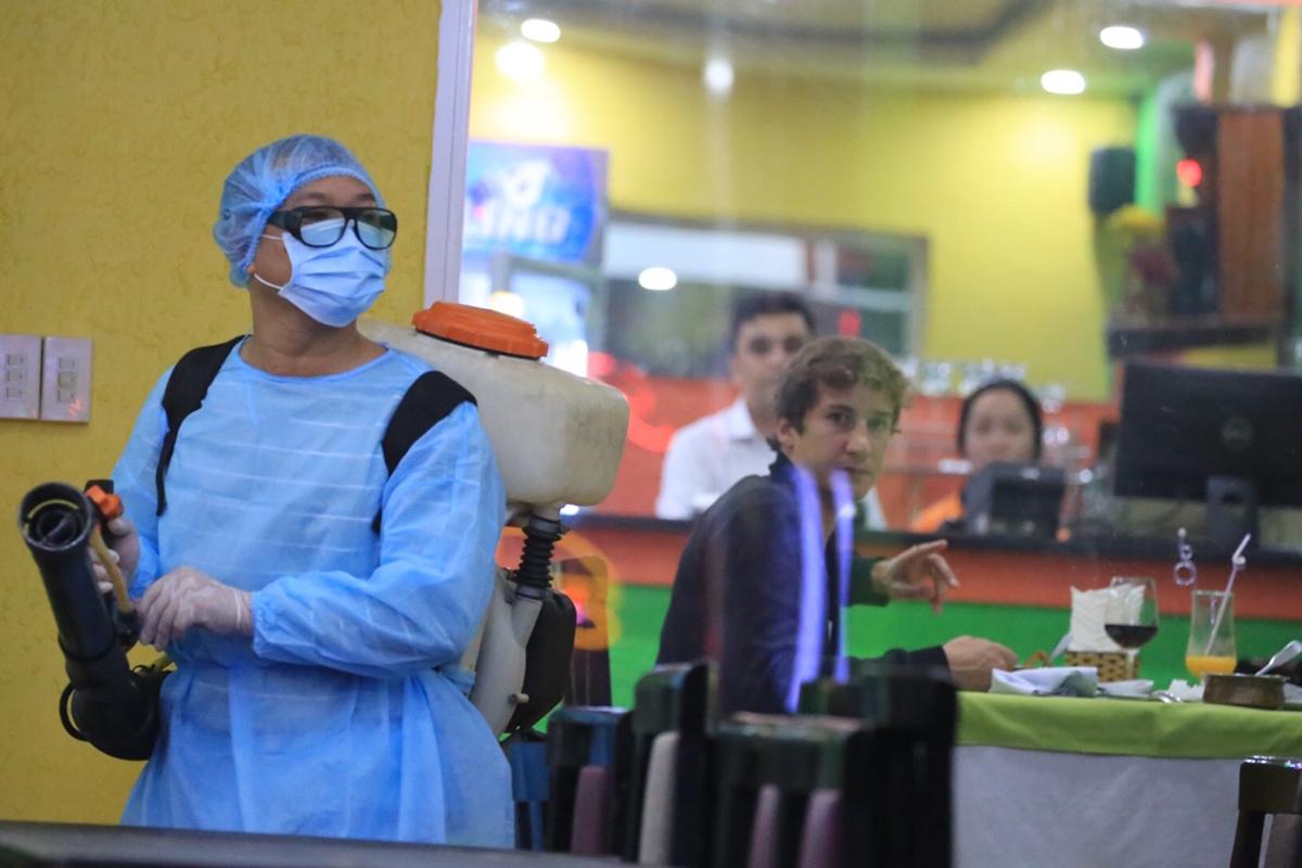 Nhân viên y tế phun thuốc khử trùng ở phố Tây. Ảnh: Võ Thạnh