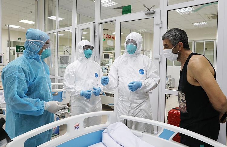 Bác sĩ Cấp trong bộ đồ bảo hộ màu xanh (ngoài cùng bên trái), đi thăm các bệnh nhân Covid-19 tại Khoa Cấp cứu chiều 24/3. Ảnh: Ngọc Thành