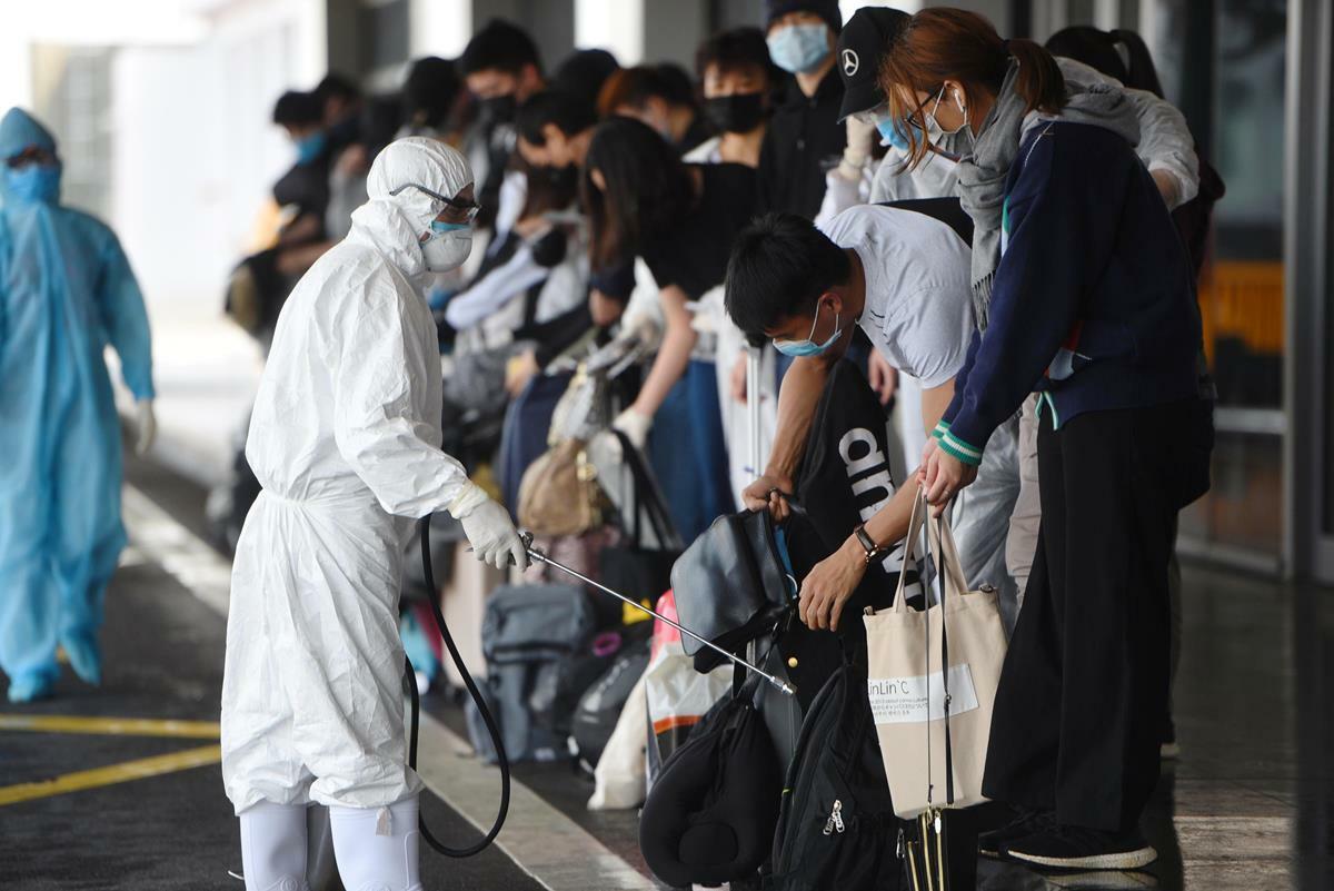 Hành khách xuống sân bay Vân Đồn được kiểm dịch nghiêm ngặt. Ảnh: Minh Cương
