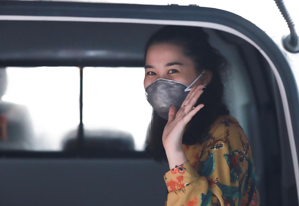 Nữ bệnh nhân tươi cười lên xe cứu thương về tự cách ly tại nhà. Ảnh: Nguyễn Đông.