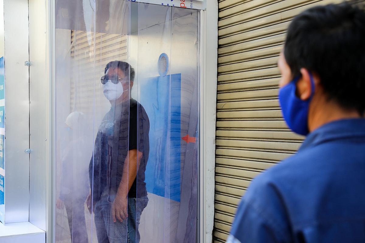 Người dân tiến hành khử khuẩn tại buồng khử khuẩn miễn phí góc đường Lê Khôi - Quách Đình Bảo (quận Tân Phú) ngày 26/3. Ảnh: Như Quỳnh.