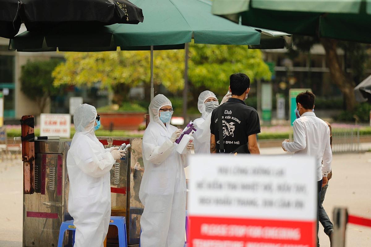 Nhân viên y tế đo thân nhiệt người ra vào Bệnh viện Bạch Mai. Ảnh: Giang Huy.
