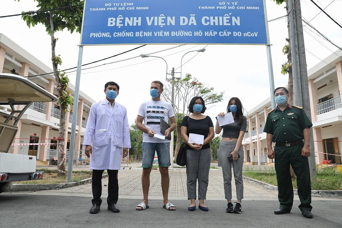 3 bệnh nhân chụp hình lưu niệm cùng bác sĩ, cán bộ Bệnh viện Dã chiến Củ Chi trước khi rời viện. Ảnh: Hữu Khoa.