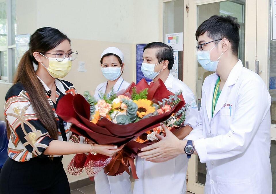 Bệnh nhân 32 (trái) tặng hoa đến các bác sĩ tỏ lòng cám ơn, khi ra viện chiều 31/3. Ảnh do gia đình cung cấp.