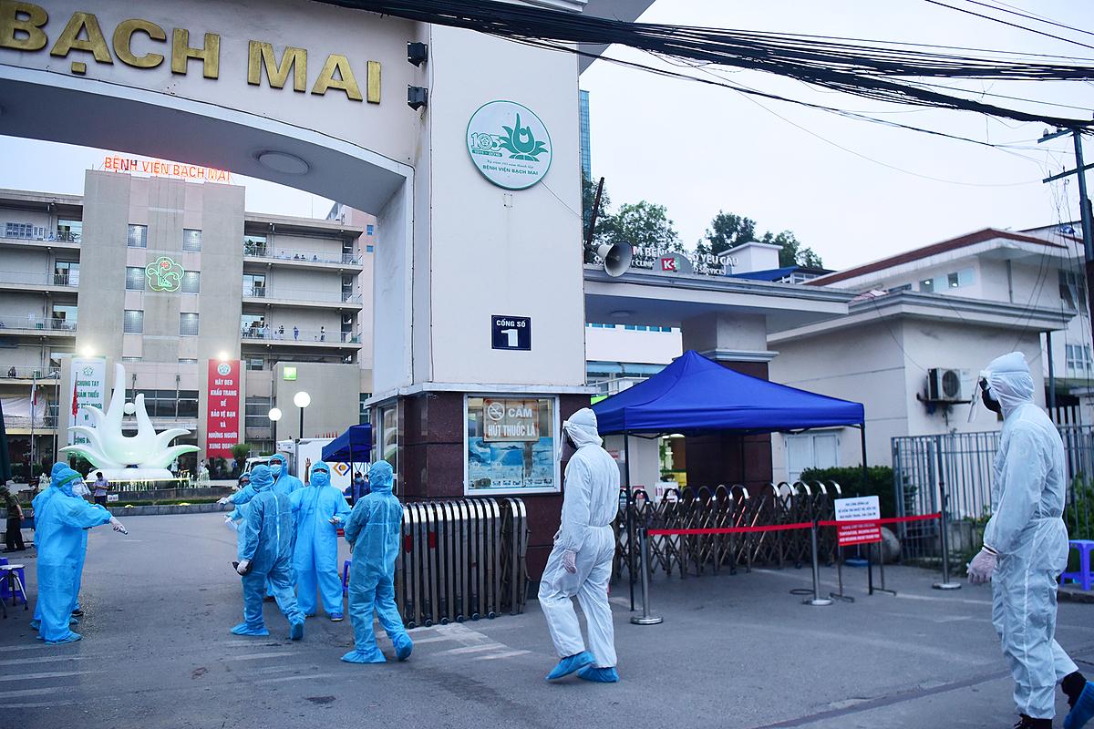 Đo thân nhiệt tại cổng Bệnh viện Bạch Mai. Ảnh: Giang Huy.