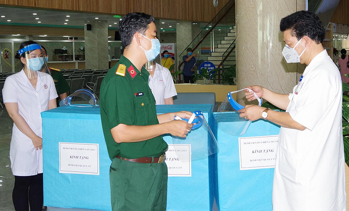Thiếu tướng Nguyễn Hồng Sơn, Giám đốc Bệnh viện Quân y 175 (áo trắng, bên phải) tiếp nhận nón kính bảo hộ từ Bệnh viện Dã chiến cấp 2 số 3. Ảnh do bệnh viện cung cấp.